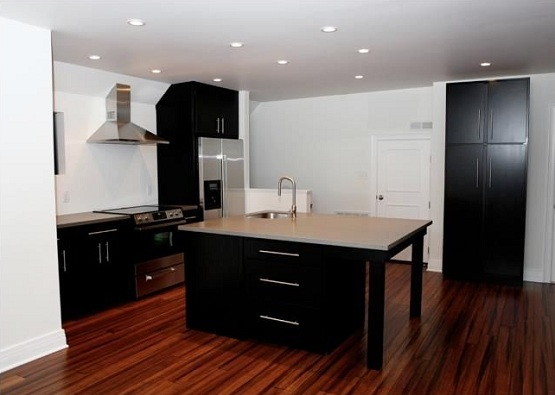 Black kitchen islands and cabinets with hand scraped bamboo flooring