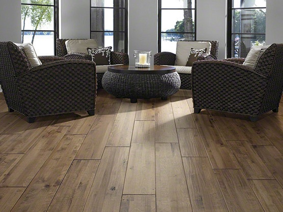 Distressed and hand-scraped wood flooring in living room with rattan furniture