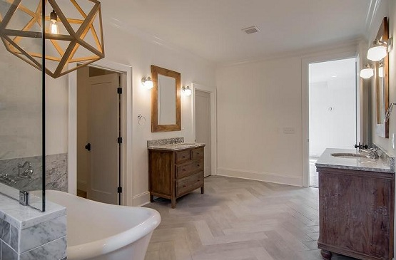 Shabby chic bathroom with herringbone pattern distressed wood flooring