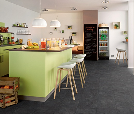 Black laminate flooring in kitchen with green kitchen island