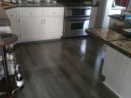 Dark laminate flooring in kitchen with white cabinet and island