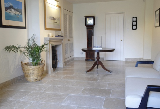 Polished limestone floor tiles in living room with fireplace