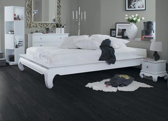 White bedroom with black laminate flooring