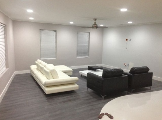 Dark grey wood laminate flooring in living room with black and white sofa