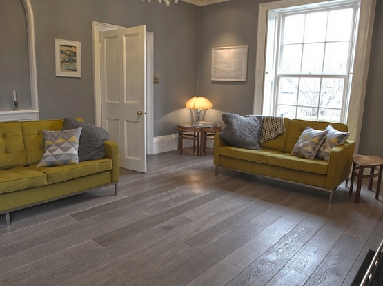 Grey wood laminate flooring in living room with yellow sofa
