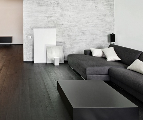 Black wooden flooring with black sofa and table