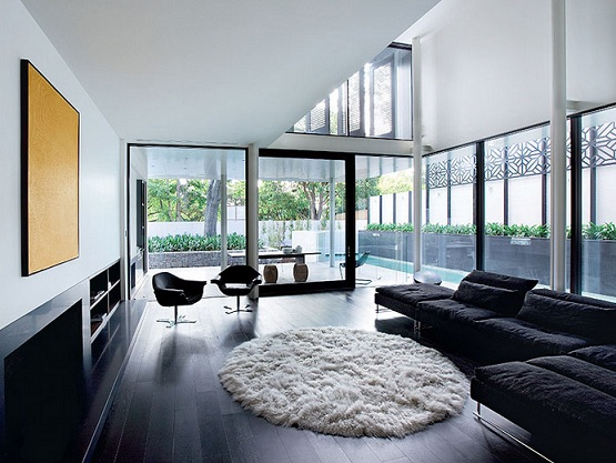 Black wooden flooring with black sofa and white round rug