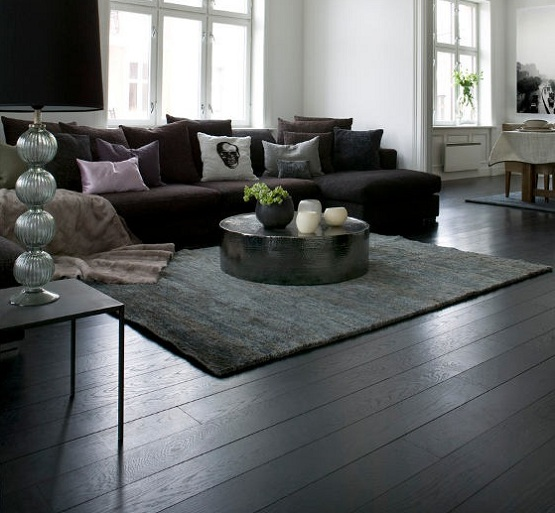 Black wooden flooring with brown sofa and round table living room