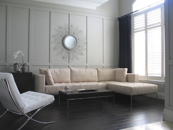 Black wooden flooring with cream sofa and gray wall paint