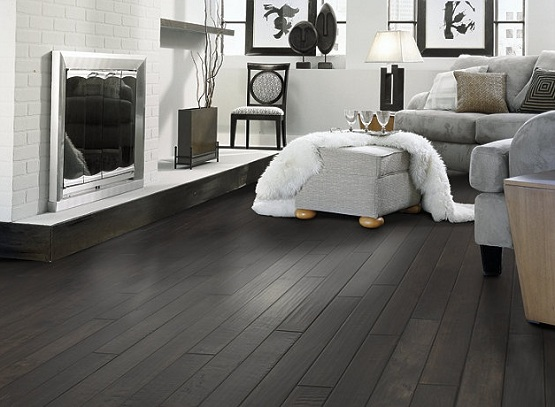Black wooden flooring with gray sofa