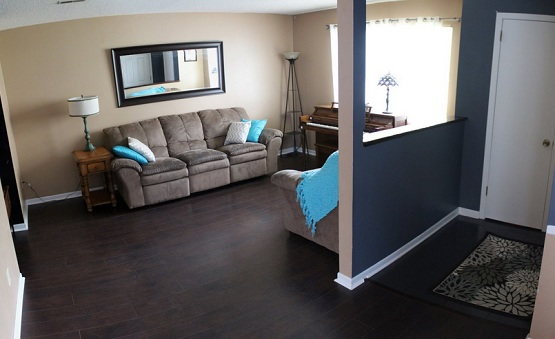 Dark brown laminate flooring in living room with brown sofa