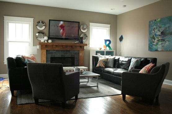 Dark brown laminate flooring in living room with fireplace and flat tv