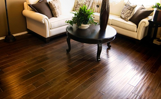 Dark brown laminate flooring in living room with round table