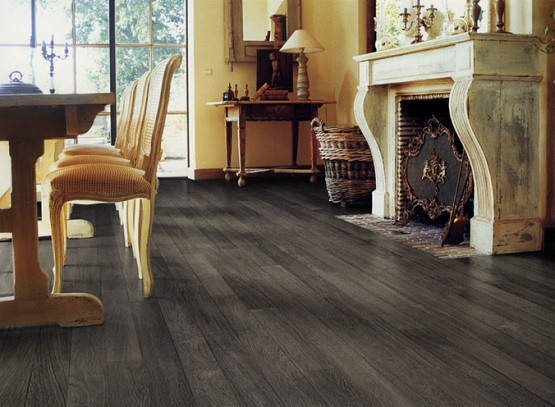 Dark grey laminate flooring in dining room with fireplace