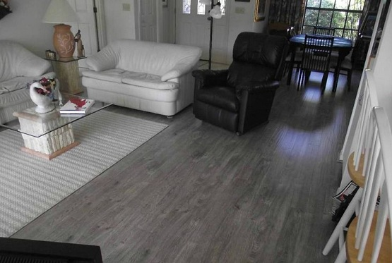 Dark grey laminate flooring in living room with black and white decor
