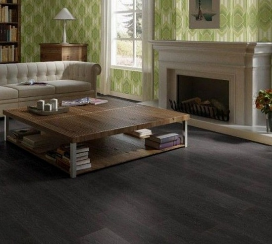 Dark grey laminate flooring in living room with fireplace and minimalis table