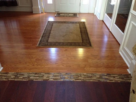 Different wood floors in house with glass tile border