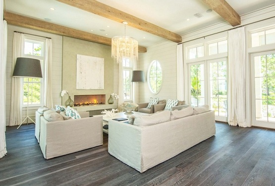 Grey wood floor stain in living room with standing lamp and fireplace