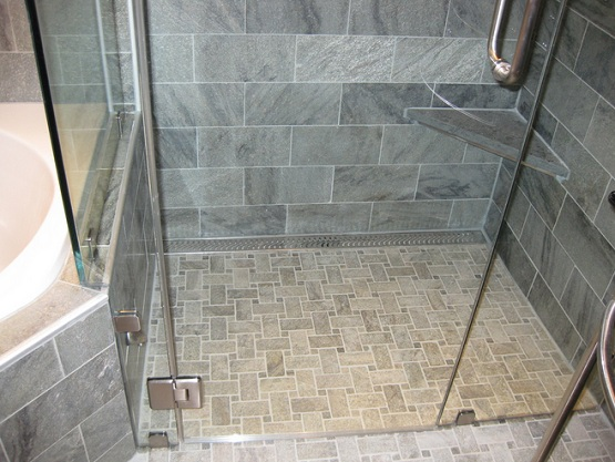 Mosaic slate tile floor in bathroom shower with glass doors